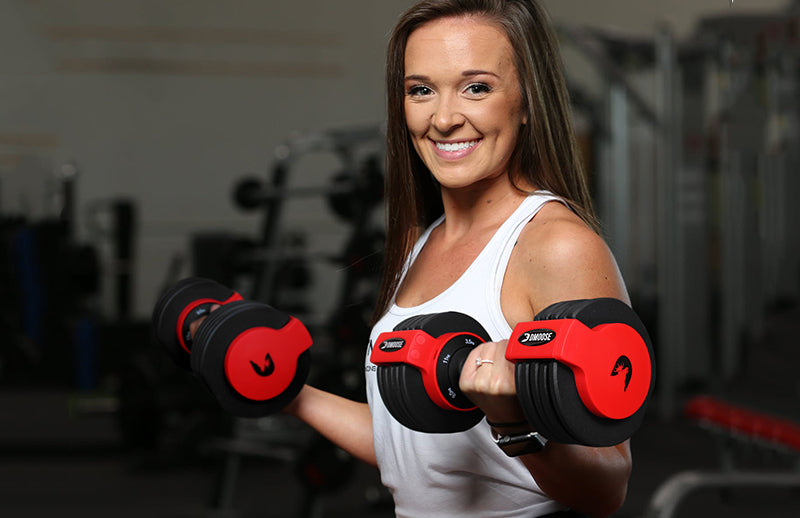 A women showing Dmoose adjustable dumbbells by holding in her hands