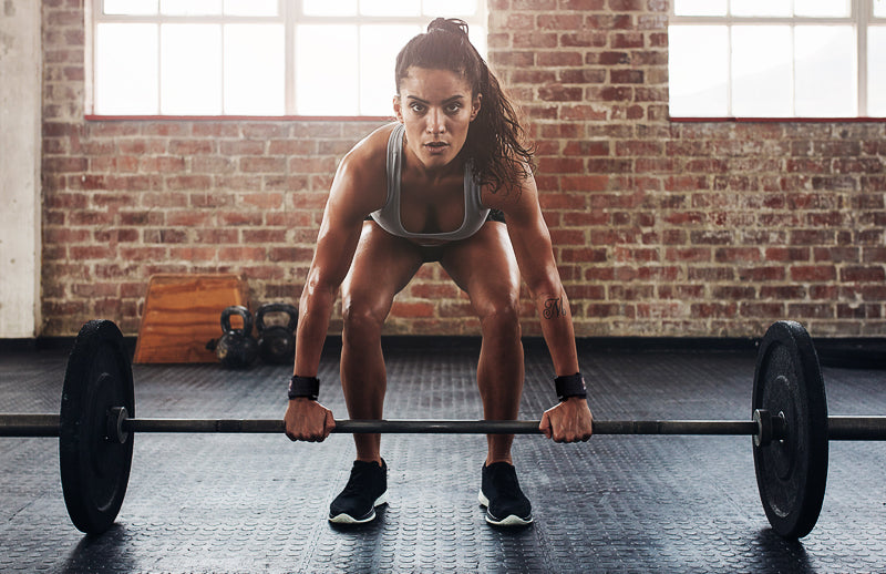 A woman is going to lift weighted barbell while wearing Dmoose crossfit hand grips