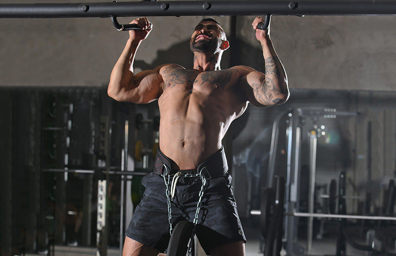A bodybuilder with tattoo on his body doing pull ups using DMoose dip belt