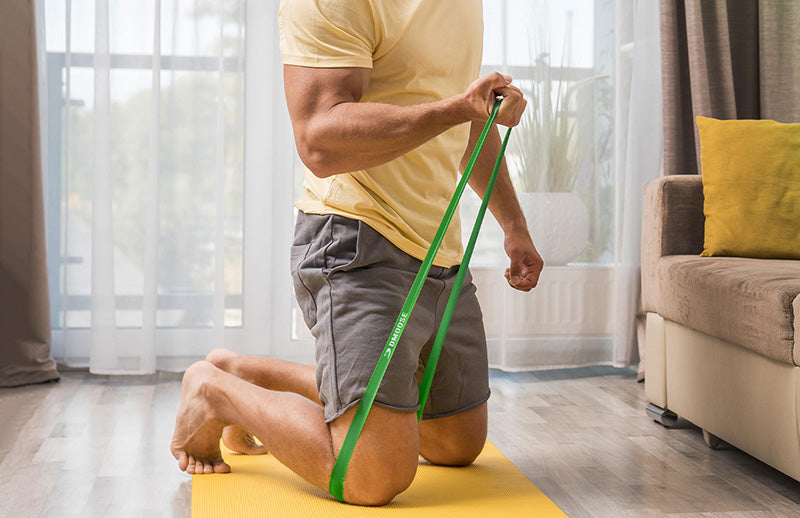 A man on yellow mat doing resistance exercise with hands using DMoose resistance band
