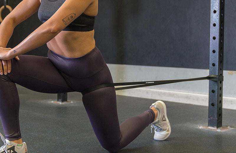 A fit woman doing Bulgarian split squat using DMoose pull up band