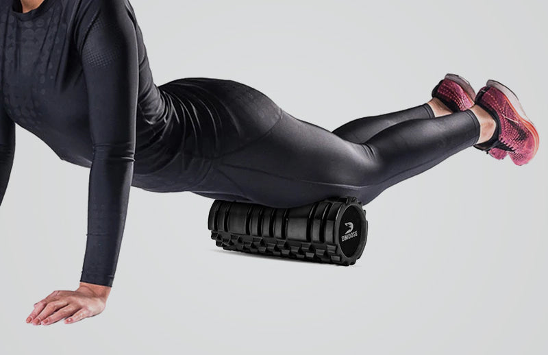 A woman placing DMOOSE foam roller under her thighs while lying in pose of push up