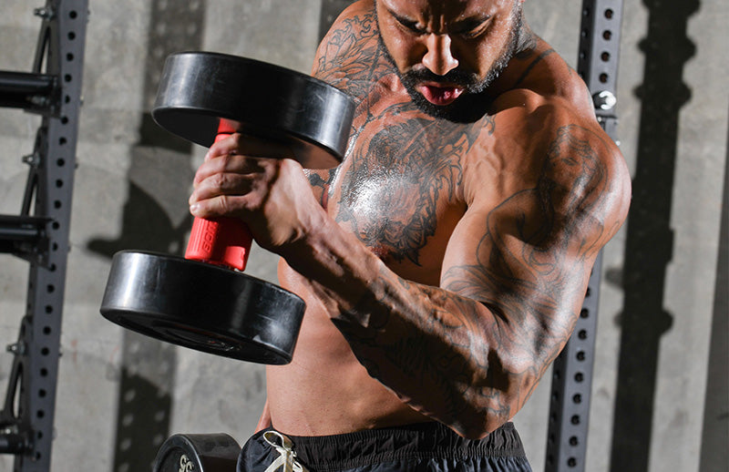 A tattooed man lifting dumbbell that is gripped with DMoose bomber grips