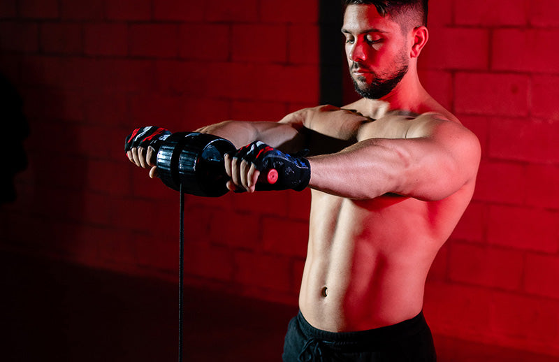 A man wearing gloves is performing wrist exercise using Dmoose wrist strengthner