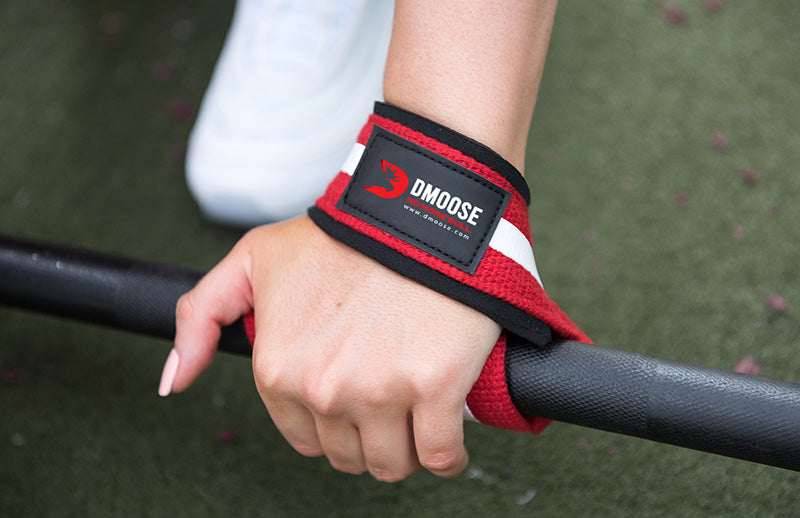 A woman with a lifting strap on her wrist is lifting a barbell