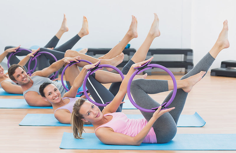 Group of people showing DMOOSE pilates circle rings by holding it in their hands