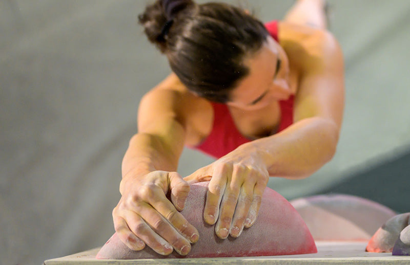 A woman climbing while using Dmoose gym chalk on her hands