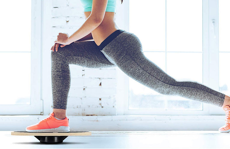 A woman stretching her legs by using DMoose balance board