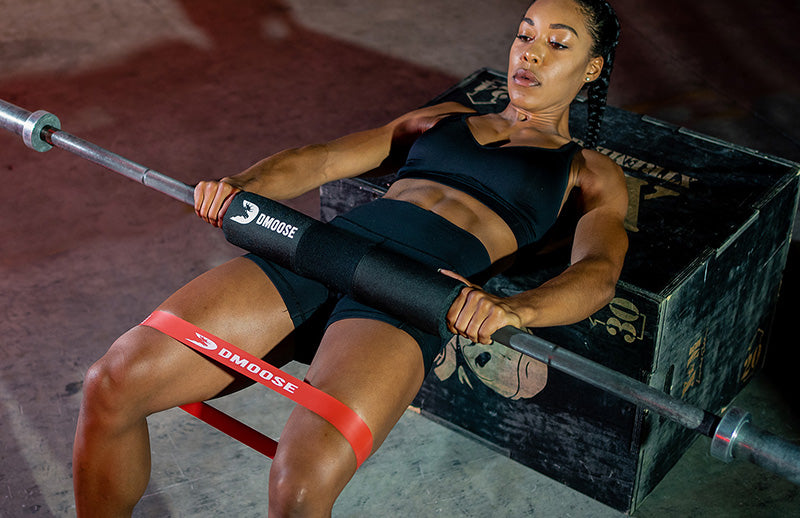 A strong woman lying on a bench wearing DMoose band on thighs and using barbell squat pad