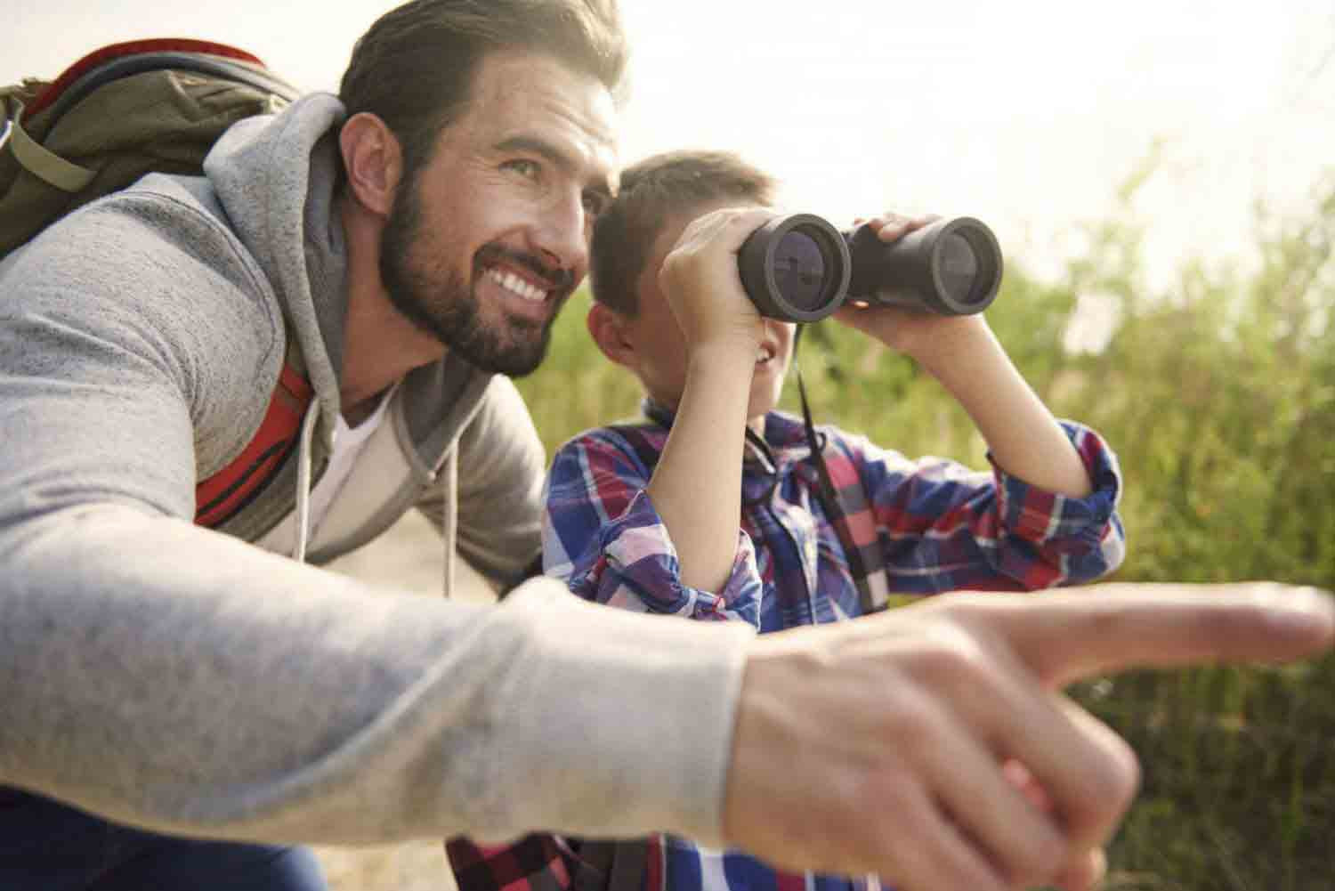 Man and son using binoculars