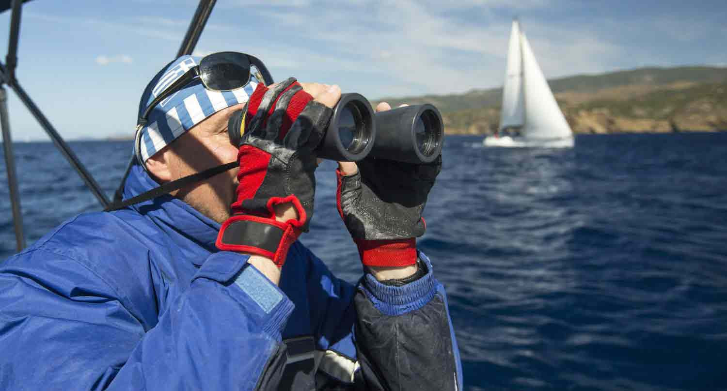 Man using binoculars on a boat