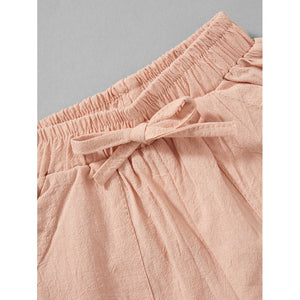 Girls ruffled short sleeves and high waist pastel coral shorts.