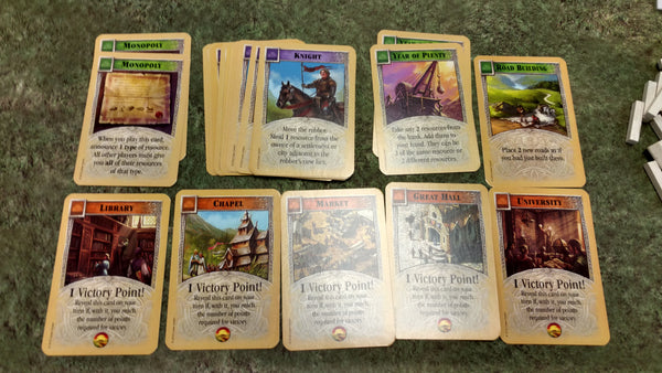 The various development cards you can find in the deck. Green progress cards, purple knights, and orange victory point cards.