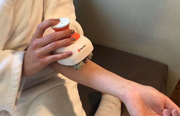 Woman relaxes using the Scalp Massager on her arm