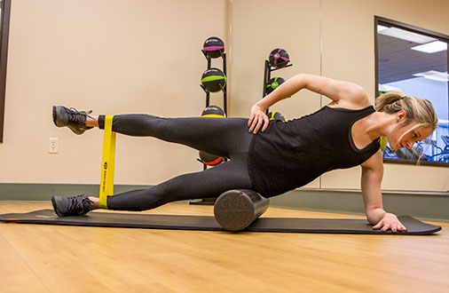 Woman stretching with band while rolling on foam roller on mat