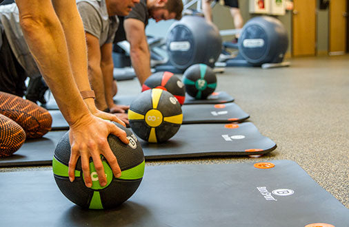 Group using medicine balls in gym