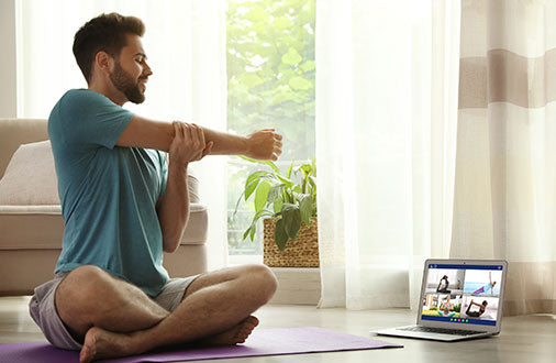 Man stretching using virtual class to workout