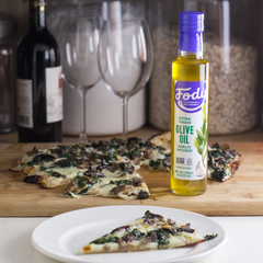 Fody Garlic-Infused Olive Oil next to a slice of pizza with wine and wine glasses in the background