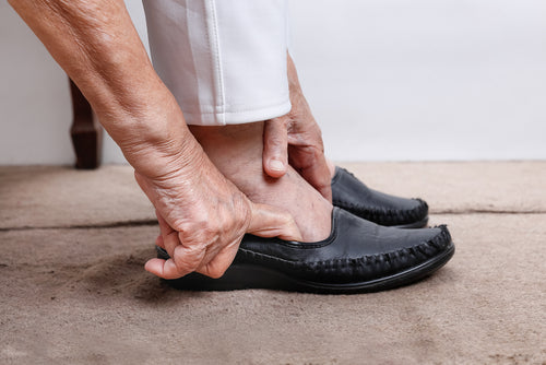 elderly woman putting on slip on shoes