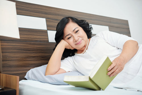 senior woman reading in bed