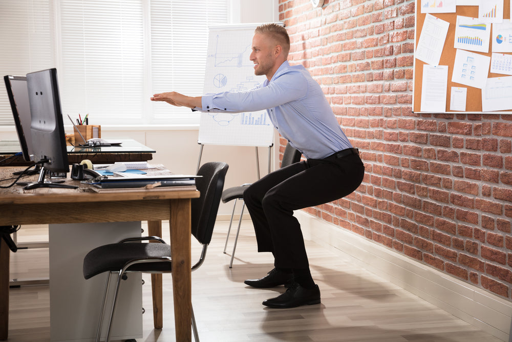 man in office performing squat