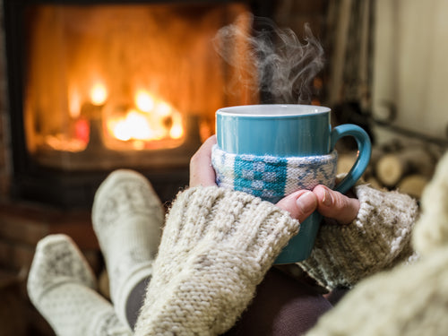 relaxing by fireplace with a hot mug