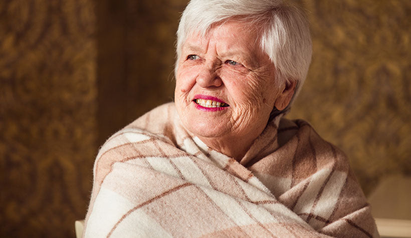 senior woman wrapped in blanket