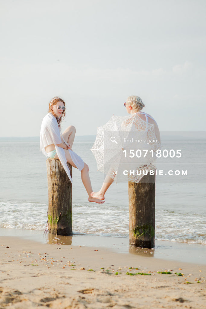150718005 |  Picturesque beach shot of two ladies in all-white beach gowns, sitting and conversing on wood pi... | Team Chuubie