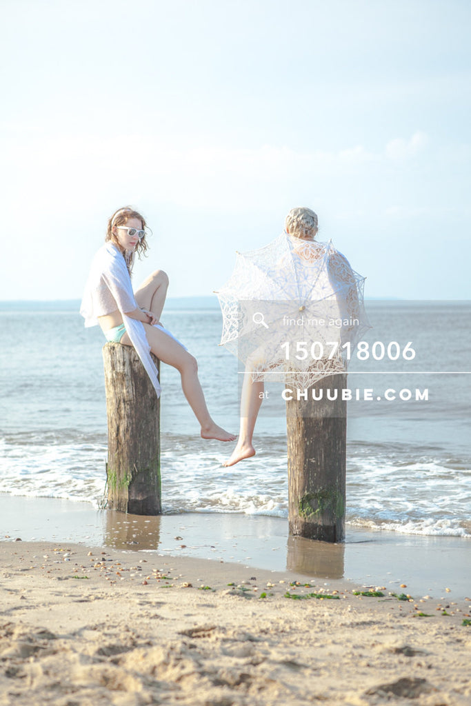 150718006 |  Picturesque beach shot of two ladies in all-white beach gowns, sitting and conversing on wood pi... | Team Chuubie