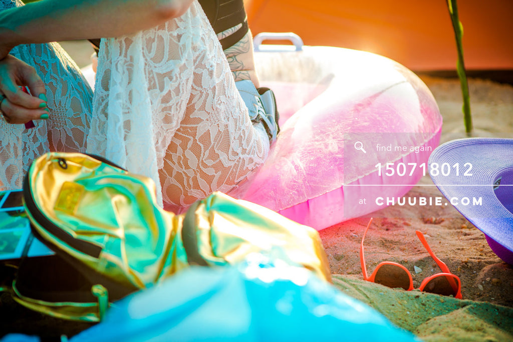 150718012 |  Lifestyle closeup: Woman in white lace pants sits of colorful pool toys reflecting sunchine on b... | Team Chuubie