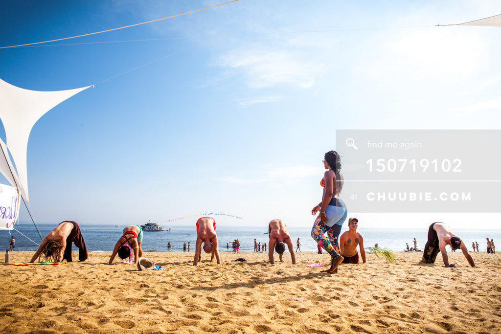 150719102 |  Downward facing dog at beach yoga session. —Gratitude Migration 2015: Summer Dream. Morning Glor... | Team Chuubie