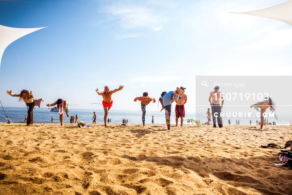 150719103 |  Group learning Virabhadrasana III (Warrior 3 Pose) beach yoga. —Gratitude Migration 2015: Summer... | Team Chuubie