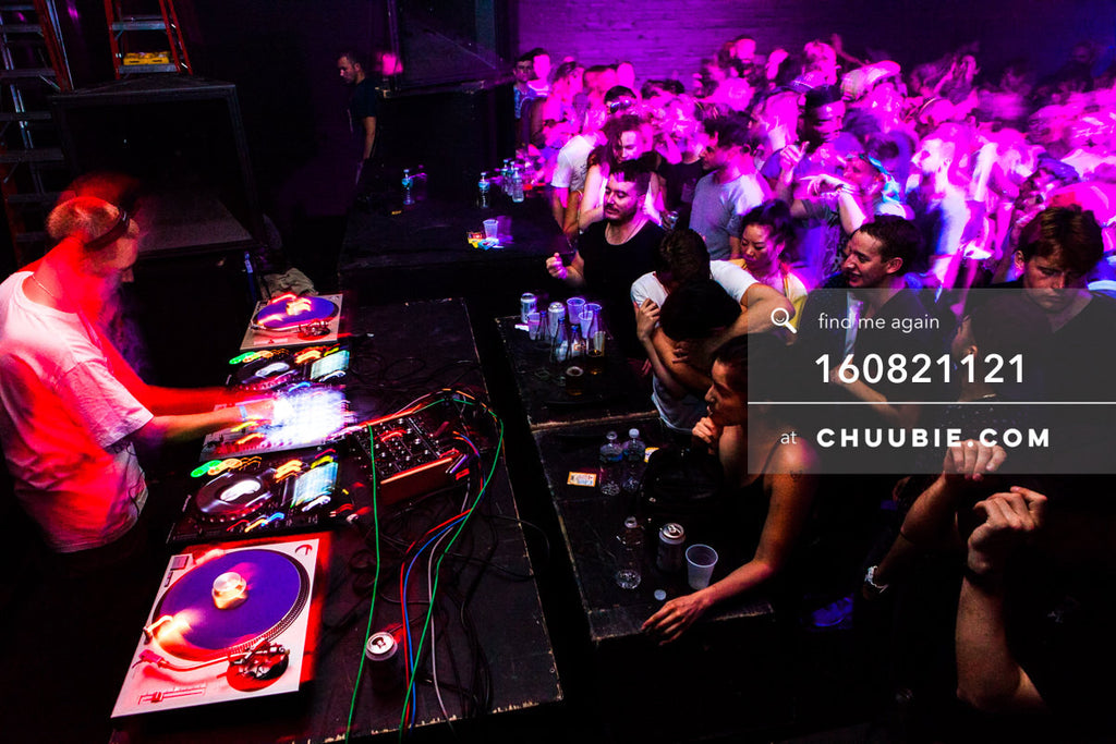 160821121 |  Side view: Joy Orbison (Peter O'Grady) DJing to a packed dance floor crowd. Ambient red and pink... | Team Chuubie