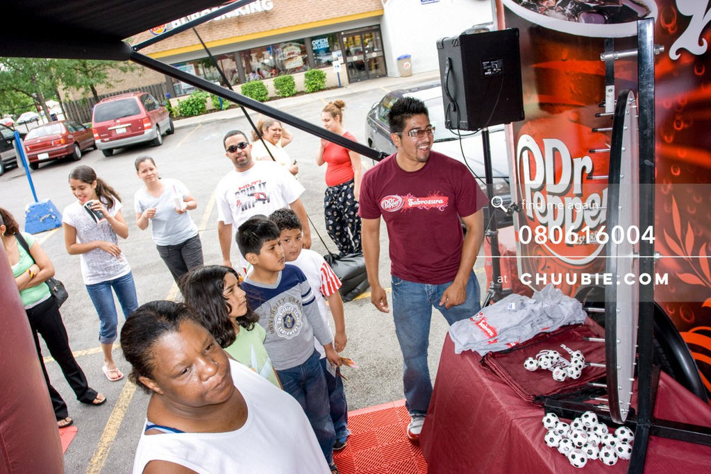 80613004 |  Local Chicago residents spin the prize wheel  —Dr. Pepper Sabrosura mobile tour event photograph... | Team Chuubie