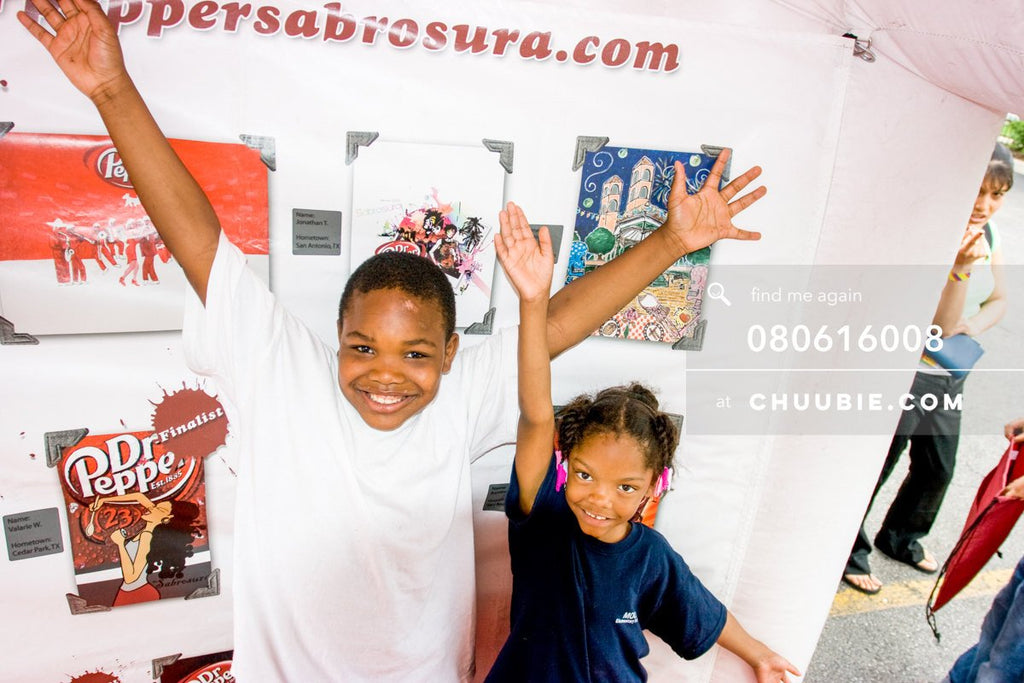 80613008 |  Young boy and girl smile with arms up in air in front of the Sabrosura art contest winning piece... | Team Chuubie