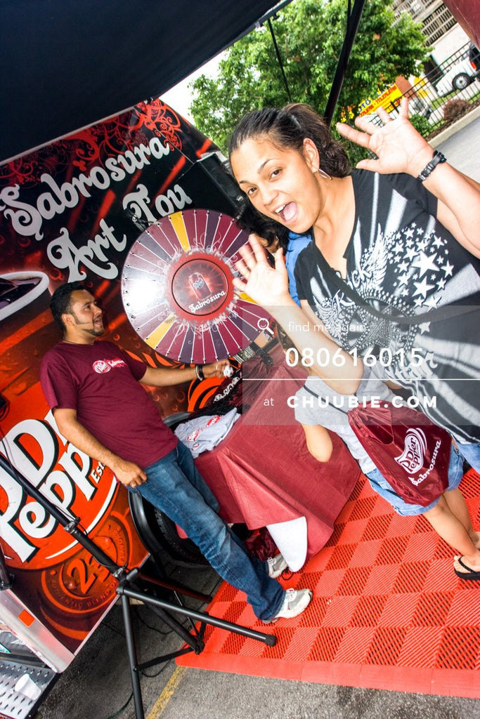80613015 |  Excited woman poses as her daughter spins the prize wheel.  —Dr. Pepper Sabrosura mobile tour ev... | Team Chuubie