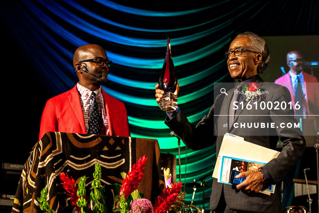 S161002016 | Reverend Al Sharpton smiling, holding up his award from United Palace, presented by Bishop Xavier... | Team Chuubie