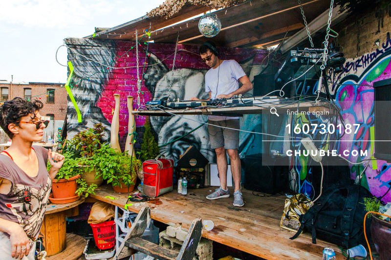 160730187 | DJ Faso (Jason Fellows) behind the decks; disco ball graffiti wall, Ilicia walking by. Brooklyn s... | Team Chuubie