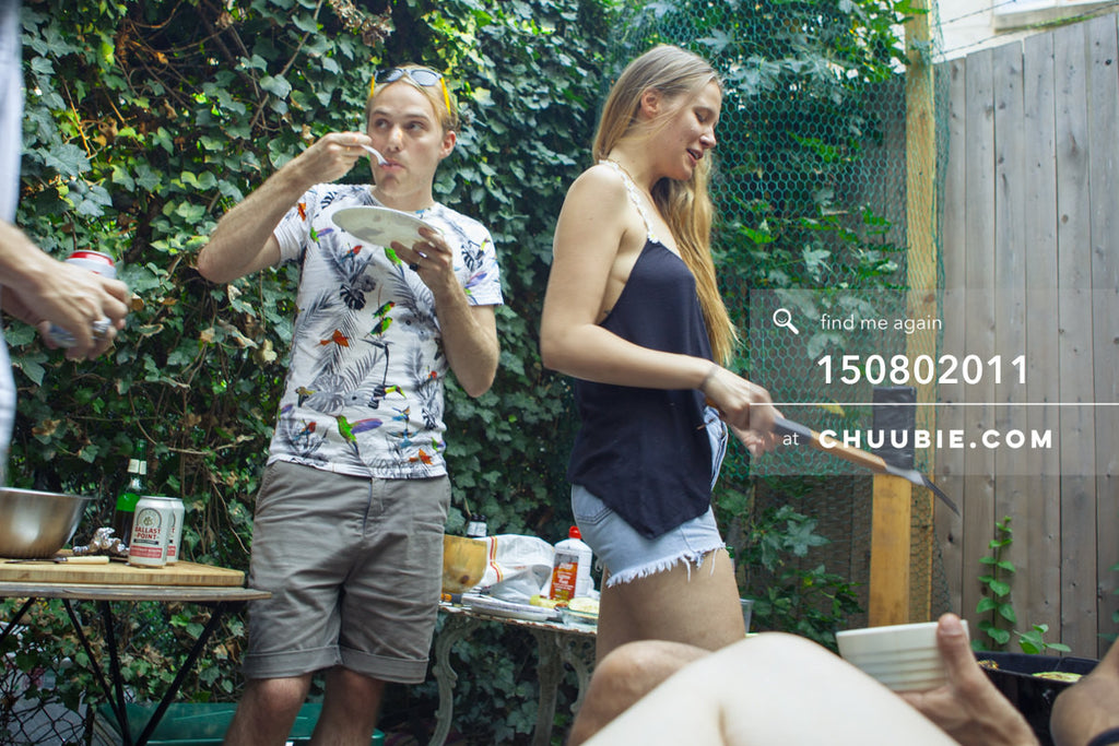 150802011 | Peter Coles in mid-bite while Lisa is at the grill in this summer backyard BBQ scene at beautiful... | Team Chuubie