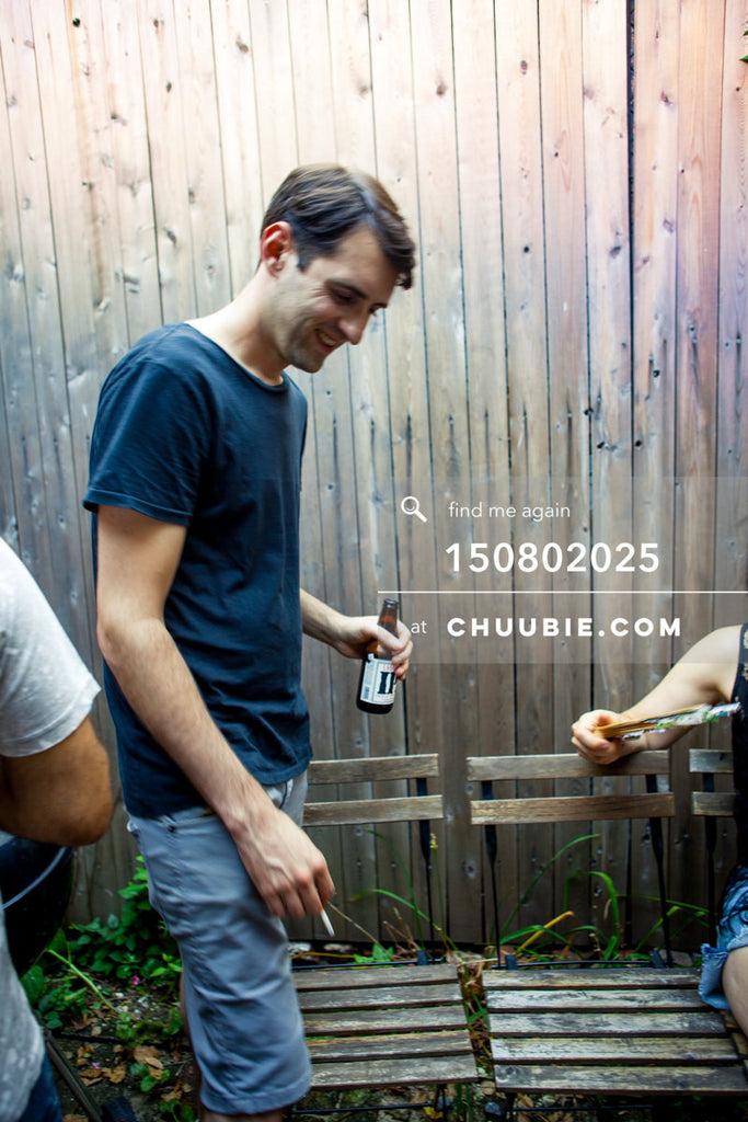 150802025 | Faso smiles with a beer at summer LES backyard BBQ. Wood fence, chairs, greenery. —Team Fun BBQ h... | Team Chuubie