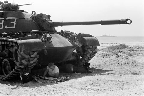 2 soldiers take five in the shade of a tank during the Marine invasion of Lebanon. film negative by Thomas O'Halloran, 1958.