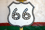 black and white vintage route 66 sign in front of a white green and red wall.