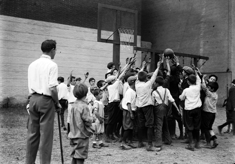 large group of children playing basketball while a school teacher with a cane looks on.