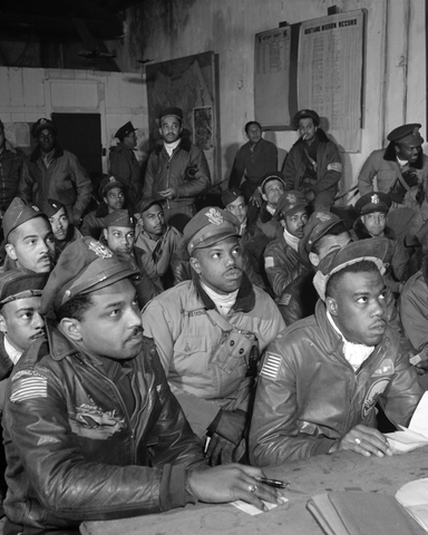Photograph shows a large group of Tuskegee airmen attending a briefing.