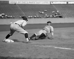 The Great Bambino slides into third base for the New York Yankees in a game against the Washington Senators. Oswald Bluege is at third. The play came  in the fourth inning on a fly out by Bob Meusel.