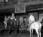women riding horses play basketball indoors.