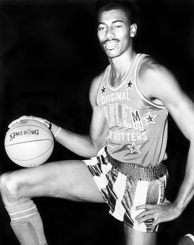 Wilt Chamberlain shown in a Harlem Globetrotter uniform. Shown kneeling while holding a Spalding basketball.
