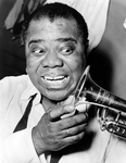 Louis Armstrong looks at his trumpet with a big smile on his face.