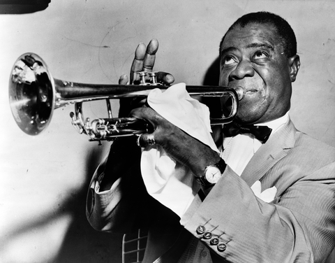 Louis Armstrong, head-and-shoulders portrait, facing left, playing trumpet.