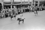 Man in full native head dress rides a horse in the Biilings Montana go west parade.